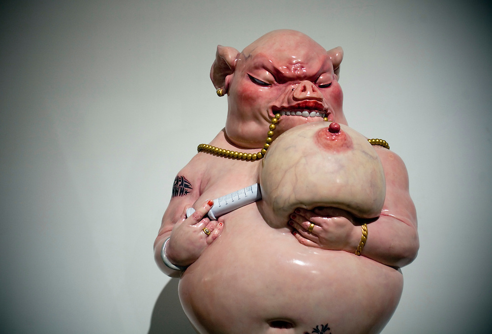 "A sculpture of a human-like pig, part of Chen Wenling's exhibition called ""The God of materialism"" on display at an art gallery in Beijing fashionable 798 art district."