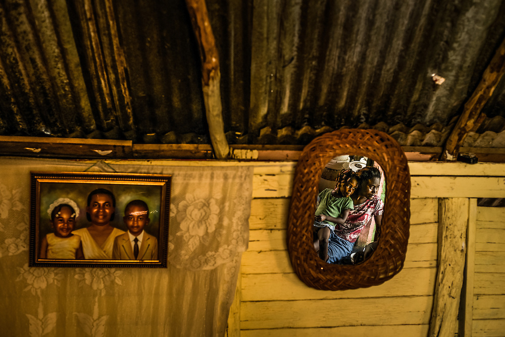 EL SEIBO, DOMINICAN REPUBLIC - OCTOBER 12, 2013: CREDIT: Lucita Edme, 27, (right) is reflected in a mirror as she talks with neighbors while sitting in the doorway of her home, with her four-year old daughter, Tatiana. Lucita was born in the Dominican Republic, and so were all of her children, but they are all now affected by judgment TC/0168, handed down by the Constitutional Court of the Dominican Republic, that essentially revokes Dominican citizenship from tens of thousands of people born in the Dominican Republic to Haitian parents, because Lucita's mother, Tata Dosine, was born in Haiti. Tata is seen in the portrait on the left, flanked by her two grandchildren, Tatiana, (left in painting), now four years old, and Moises, (right in painting) now seven years old. The family lives in an impoverished batey on a sugar plantation in El Seibo. CREDIT:  Meridith Kohut for The New York Times