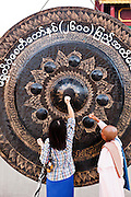 Hitting giant gong at Shwedagon Pagoda, Yangon, Myanmar.