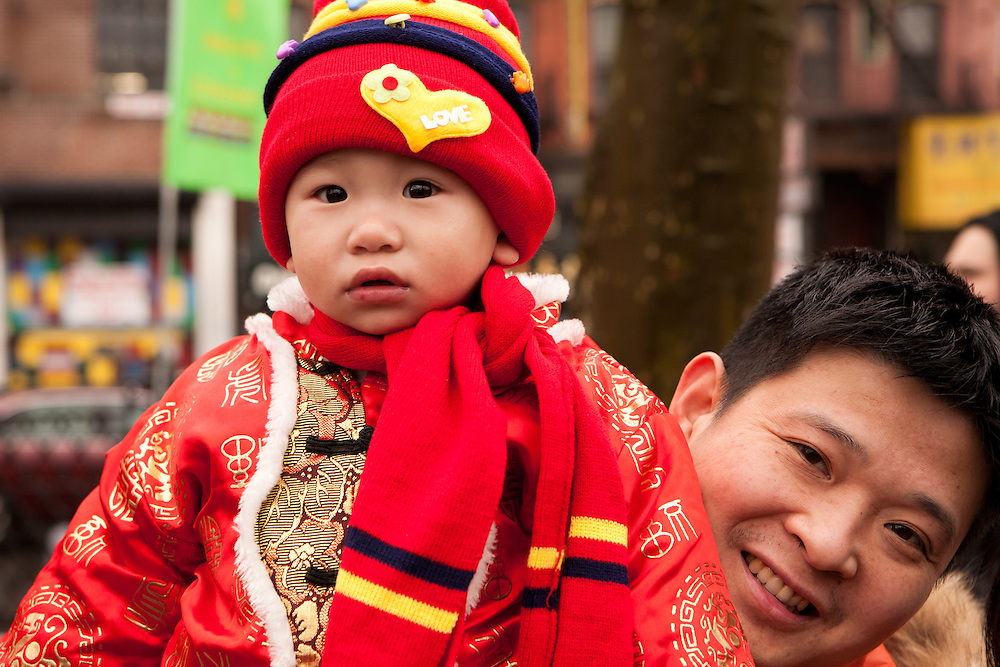 Young spectator in traditional red costumes. Red is a symbol of good luck.