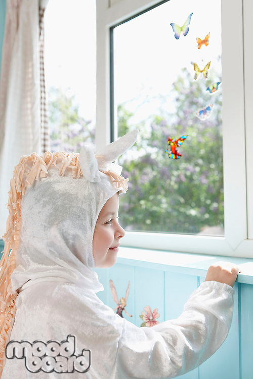 Profile of young girl (5-6) in unicorn costume opening door smiling