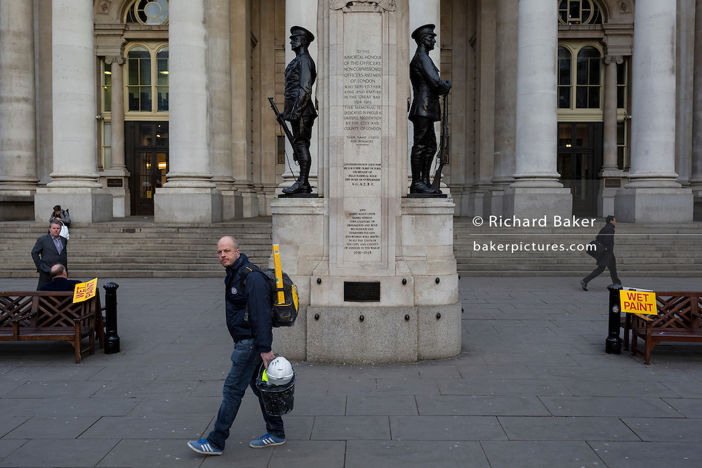 Wet Paint signs and a passing workman with a matching yellow  spirit level, on 16th February 2017, outside Royal Exchange and the WW1 memorial, in the City of London, England.