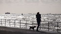 © Licensed to London News Pictures. 20/10/2017. Southsea, UK.  Rough seas off Portsmouth this morning, 20th October 2017, as a woman with her dog takes a photo of the waves. Southern England has been experiencing strong winds this morning, and is set for stronger winds as Storm Brian approaches from the Atlantic. Photo credit: Rob Arnold/LNP