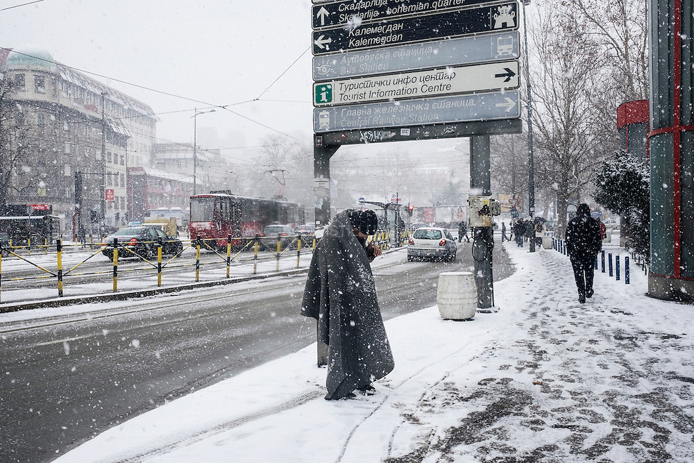 An Afghan refugee standing under the snowfall. Thousands of refugees and migrants are grappling with freezing conditions as severe winter weather sweeps across Serbia.