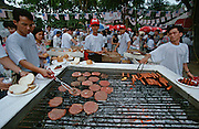 4th of July party at the U.S. Embassy. Americans and Vietnamese celebrating and grilling hamburgers together.
