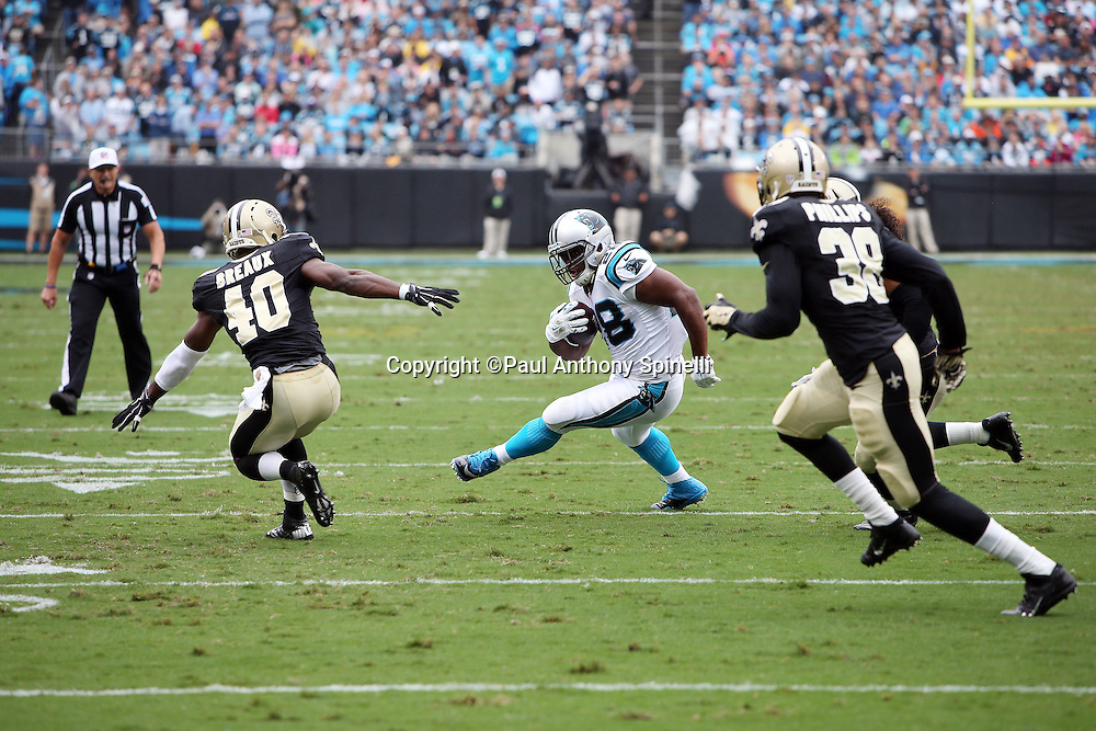 Carolina Panthers running back Jonathan Stewart (28) runs the ball while being chased by New Orleans Saints cornerback Delvin Breaux (40) and New Orleans Saints cornerback Brandon Browner (39) during the 2015 NFL week 3 regular season football game against the New Orleans Saints on Sunday, Sept. 27, 2015 in Charlotte, N.C. The Panthers won the game 27-22. (©Paul Anthony Spinelli)