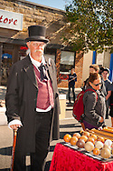 Wearing vintage suit of top hat, vest, morning jacket with long tails, tall mustached senior man next to vintage baseball display at Merrick Street Fair in Merrick, New York, USA, on October 22, 2011