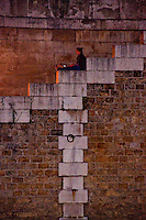 Paris, woman sitting on the stone steps leading down to the river Seine.