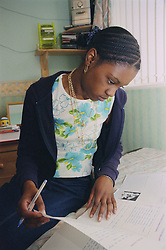 Teenage girl sitting on bed studying from notes,