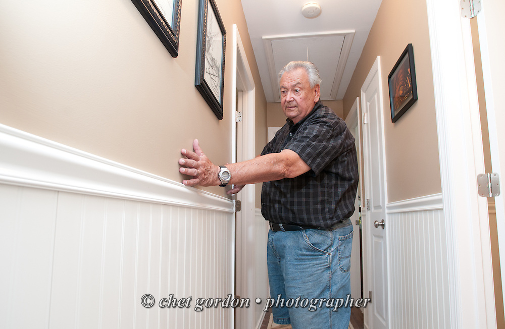 Ron Colvin examines the sheetrock, new wall molding, and wainscoting in the hallway of their Waretown, NJ beach house on Sunday, August 7, 2014. Their home was severely damaged after Hurricane Sandy in 2012. They hired a contractor for repairs who did shoddy work and never completed the job, leaving the house unusable. They finally were able to hire a second contractor through Angie's List  (Bob Caccamo, owner of Sure Thing Home Remodeling) to re-do everything, including sheetrock, trim, moldings, wainscoting, tile, paint door installation and extensive work to their master bathroom. Caccamo finished the work in record time and at a fair price.  © Chet Gordon for Angie's List
