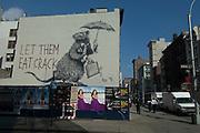 """Banksy graffiti, """"LET THEM EAT CRACK"""" rat with breif case full of money. Howard Street, Manhattan, New York."""