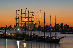 Woolwich, London, September 14th 2016. The sun sets behind the skyscrapers of Docklands and the Tall ships gathered for the Sail Greenwich Festival 2016 on the River Thames at Woolwich.  &copy;Paul Davey<br /> FOR LICENCING CONTACT: Paul Davey +44 (0) 7966 016 296 paul@pauldaveycreative.co.uk