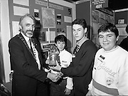 05/01/1989.01/05/1989.5th January 1989.The Aer Lingus Young Scientist of the Year Award at the RDS, Dublin ..Picture shows Peter MacMenamin, President of the Teachers Union of Ireland presenting trophy to pupils from Firhouse Community College, Tallaght, Dublin from left Debbie Staunton, Kevin Whelan and Trevor McBride for their project 'The Wildlife of the Dodder Valley'.