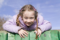 Little girl having fun at an adventure playground,