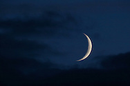 Middletown, N.Y. -  The crescent moon shines through the clouds on the evening of Oct. 14, 2007.