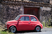 Bright red colour dusty old Fiat 500 Cinquecento early version - typical Italian small city car in Sicily, Italy