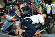 Rach Gia. Young boy having a nap on a motorbike.