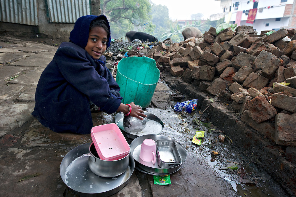 In this slum in Varanasi, many girls are responsible for washing the dishes in dirty surroundings.