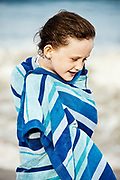 Cute young girl drying off with a beach towel, Cape Cod, Massachusetts, USA.