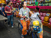24 NOVEMBER 2015 - BANGKOK, THAILAND:  A woman on a bike rides through the carnival games at the Wat Saket temple fair. Wat Saket is on a man-made hill in the historic section of Bangkok. The temple has golden spire that is 260 feet high which was the highest point in Bangkok for more than 100 years. The temple construction began in the 1800s in the reign of King Rama III and was completed in the reign of King Rama IV. The annual temple fair is held on the 12th lunar month, for nine days around the November full moon. During the fair a red cloth (reminiscent of a monk's robe) is placed around the Golden Mount while the temple grounds hosts Thai traditional theatre, food stalls and traditional shows.       PHOTO BY JACK KURTZ