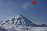 Scientists on snowmobile pull tethered weather blimp into position on outskirts of the international science village of Ny-Alesund on Spitsbergen island in Kongsfjorden; Svalbard, Norway.