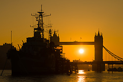 © Licensed to London News Pictures. 10/10/2018. London, UK.  Sunrise behind Tower Bridge and HMS Belfast on the River Thames during warm and sunny weather this morning.  Photo credit: Vickie Flores/LNP