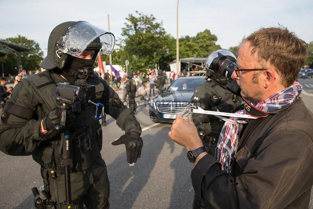 Hamburg, Germany - 07.07.2017<br /> <br /> G20-Gipfel in Hamburg. Ein Journalist zeigt seinen Presseausweis und die Akkreditierung nachdem Beamte ihn aufforderten den Abstand von Polizeikr&auml;ften zu nehmen, welche sch&uuml;tzend vor blockierten G20-Delegationsfahrzeugen stehen.<br /> <br /> Photo: Bjoern Kietzmann