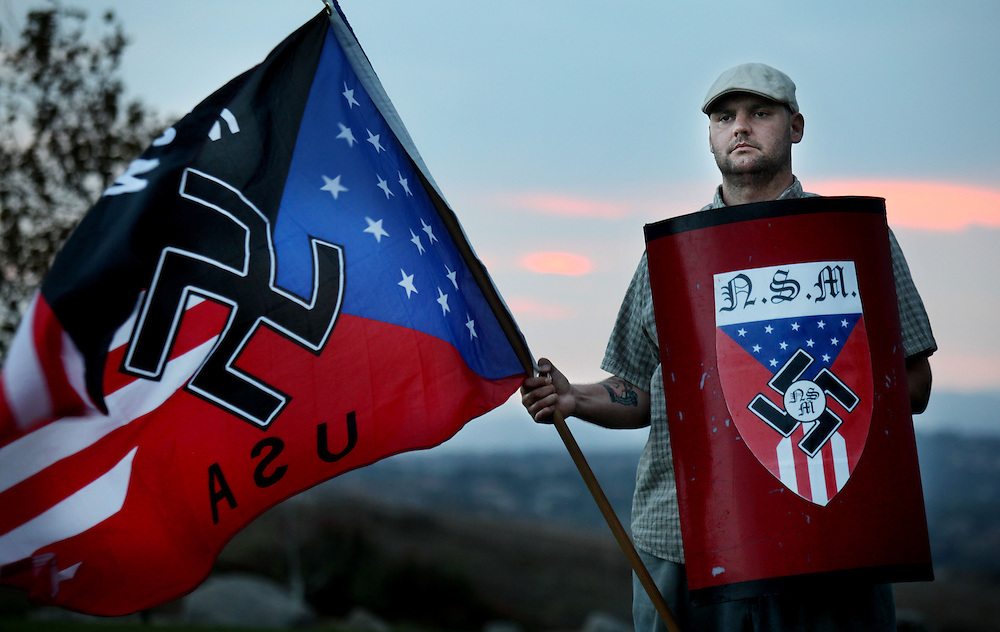 Jeff Hall holds a Neo Nazi flag while standing at Sycamore Highlands Park near his home in Riverside, California on Friday, October 22, 2010.  Hall is running for the Riverside Municiple Water Board and is a Neo Nazi supporter.(AP Photo/Sandy Huffaker).STORY SLUG:  NEO NAZI CANDIDATE