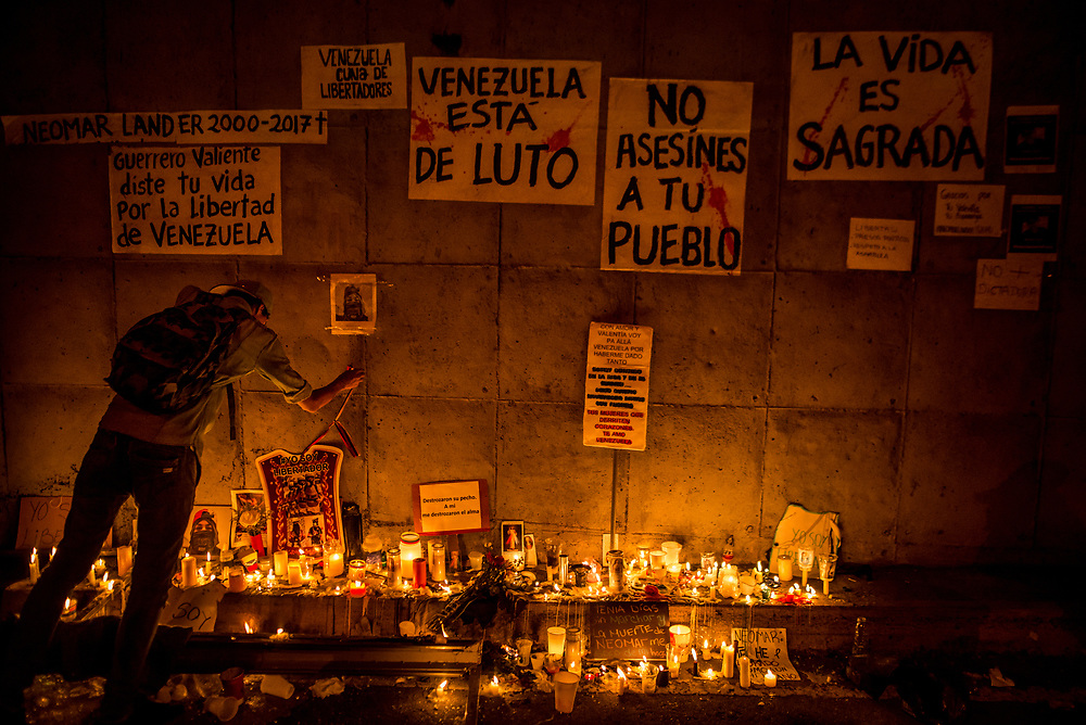 """CARACAS, VENEZUELA - JUNE 8, 2017: Member of """"The Resistance"""", Johan Caldera mourns the death of his close friend, Neomar Lander, 17, at a makeshift altar in the spot where Mr. Lander was killed by security forces during an anti-government protest in Caracas. Mr. Caldera said he is even more determined to protest since his friend was killed.  """"Now, I have no fear - because I already lost the fear I had, and the respect for the military. The little respect I had, is gone. Now, the real soldiers of Venezuela wear rags on their faces, they wear a glove and they they don't use grenades - they use stones, they use their will, and they use their balls to go out into the street."""" He said he had discussed with Neomar the possibility of being killed during the protests, """"and he [Neomar] told me: brother, if I die - if I lose my life during a protest, I don't want everyone to stop marching, I want them to march double and keep going to the street for a week, every single day, day and night without fear.""""  PHOTO: Meridith Kohut"""