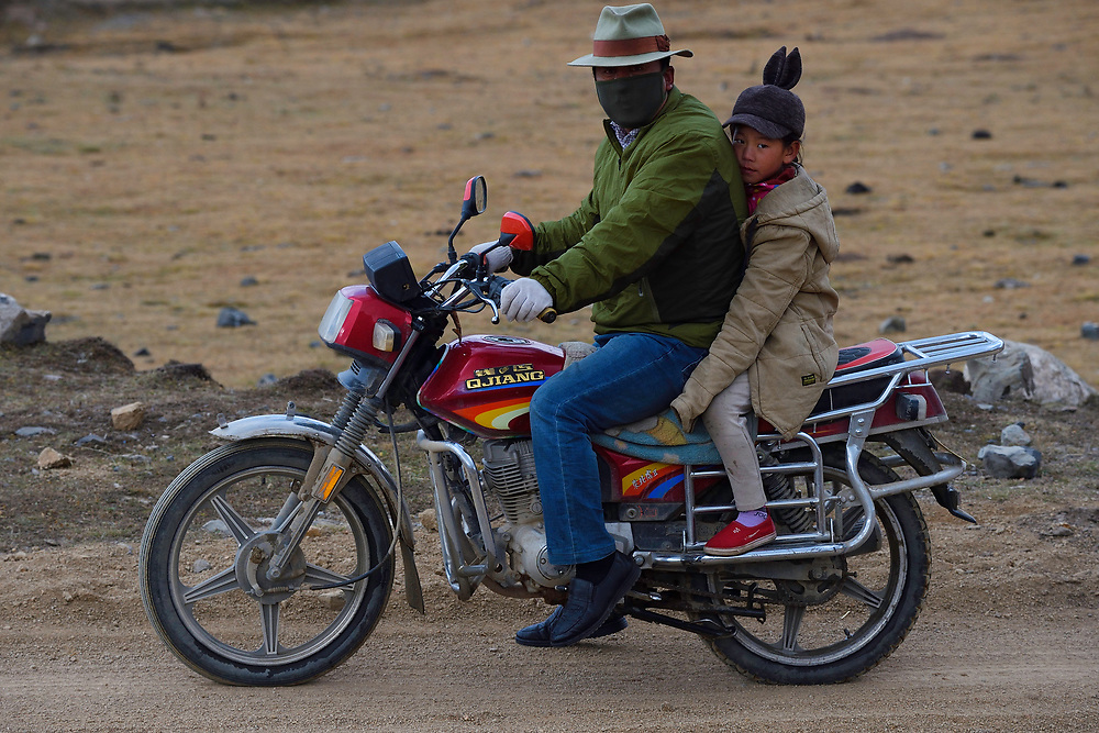 Tibetan shepherd dad with his daughter on the back of the motor bike, Tibetan Plateau, Qinghai, China