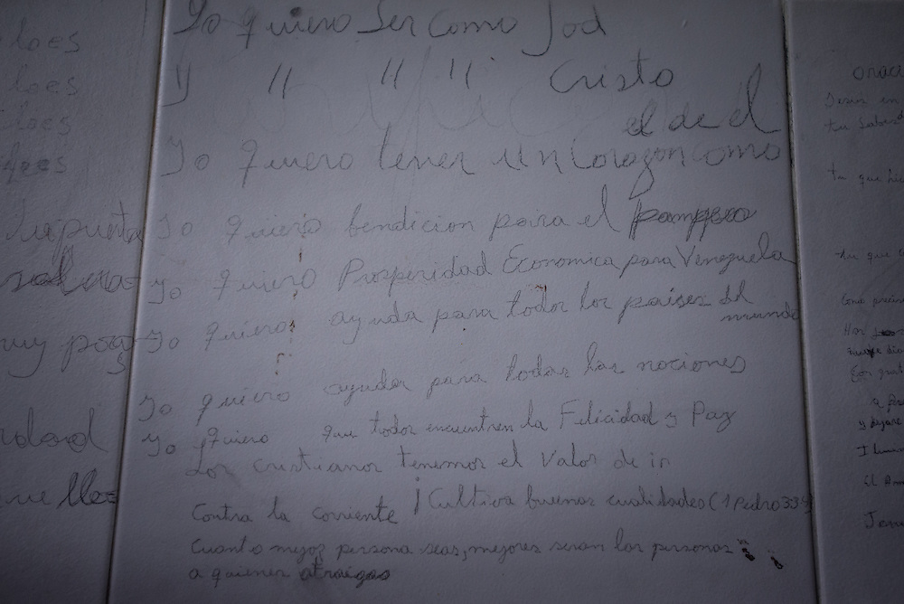 "BARQUISIMETO, VENEZUELA - JULY 29, 2016: Schizophrenic patient, Priscialiano Rosendo wrote on the wall: ""I want economic prosperity for Venezuela"" among other things he wishes for. Rosendo is violent when he does not have his medication. He has also been diagnosed with mystical religious delusions. He gorged out his own eye when he was unmedicated.  Since, he has become a devout evangelical Christian, and has covered the walls outside of his hospital room with religious writings. The economic crisis that has left Venezuela with little hard currency has also severely affected its public health system, crippling hospitals like El Pampero Psychiatric Hospital by leaving it without the resources it needs to take care of patients living there, the majority of whom have been abandoned by their families and rely completely on the state to meet their basic needs. The hospital has not employed a psychiatrist for over two years. Drugs used to combat bipolar disorder, epilepsy, schizoaffective disorder and chronic anxiety are now in short supply, as are numerous sedatives and tranquilizers needed to care for patients. Members of the nursing staff debate daily which patients are the most unstable, to decide which patients will receive pills and which will go without. When a patient loses control, often the only thing they can do is restrain them, or lock them in an isolation cell to prevent them from hurting themselves, other patients and members of the staff.  PHOTO: Meridith Kohut for The New York Times"