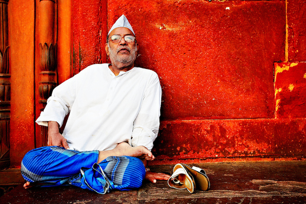 A man sitting inside Jama Masjid waiting for the evening prayer to start, New Delhi, India.
