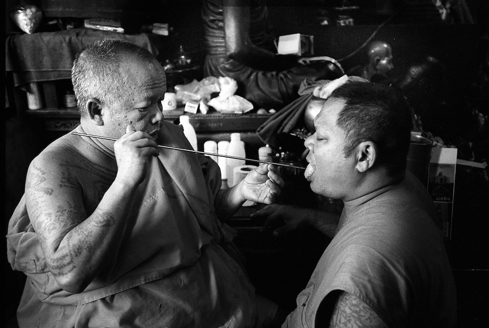 Tattoo Festival at Wat Bang Phra, a Buddhist temple in the town of Nakhorn Chaisri, Thailand - men adorned by Thai Monks with tattoos representing animal spirits often go into a trance claiming they are possessed  by the spirit of the animal. This Monk is having symbols tattooed on his tongue. March 2003.©David Dare Parker/AsiaWorks Photography