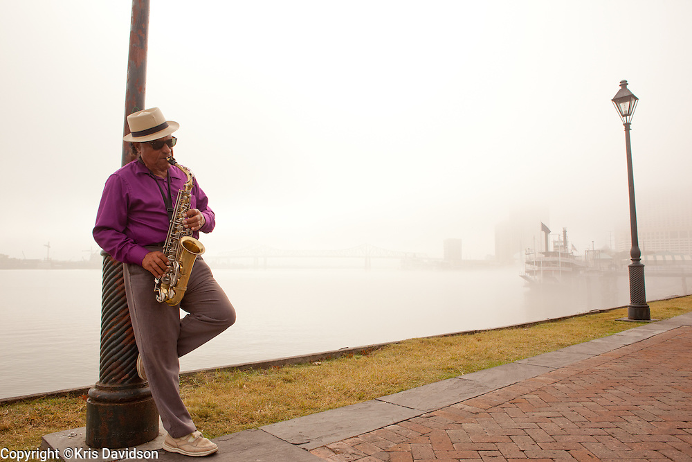 Musician playing for tips by the Mississippi River in New Orleans.