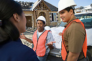 Architect and two construction workers having discussion on construction site