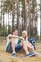Full length of young hiking couple relaxing in forest