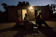 MBOUR - SENEGAL: Villagers hang out outside their homes newly equipped with solar powered lamps in an off grid village in August 07 2017 near Mbour, Senegal. Despite the high growth and expectations on Senegalese economy, many rural areas still live without power.