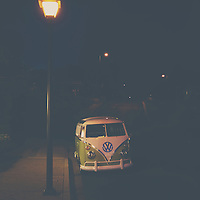 a volkswagen bus sits under a street light on a street in Morro Bay, california.