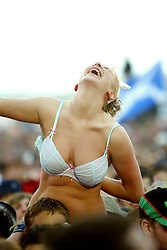 Fan wearing a bikini top, at the main stage watching The Charatans, at T in the Park, July 10, 2004..©Michael Schofield.