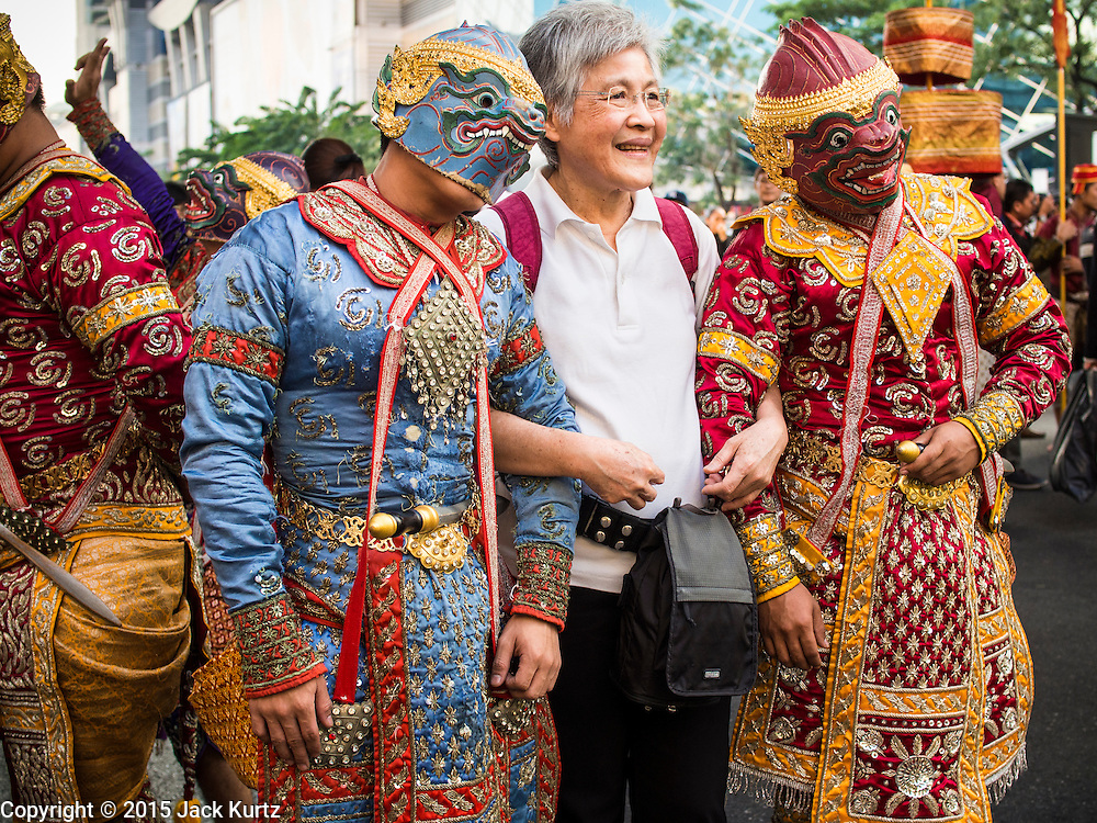 """14 JANUARY 2015 - BANGKOK, THAILAND:  A tourist poses for pictures with men in the costumes of the Thai monkey army, a popular character from Thai mythology, during the 2015 Discover Thainess parade. The Tourism Authority of Thailand (TAT) sponsored the opening ceremony of the """"2015 Discover Thainess"""" Campaign with a 3.5-kilometre parade through central Bangkok. The parade featured cultural shows from several parts of Thailand. Part of the """"2015 Discover Thainess"""" campaign is a showcase of Thailand's culture and natural heritage and is divided into five categories that match the major regions of Thailand – Central Region, North, Northeast, East and South.    PHOTO BY JACK KURTZ"""