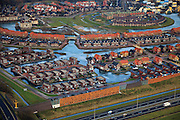 Nederland, Gelderland, Beuningen, 10-01-2011;.Nieuwbouwwijk in Beuningen met rechtsboven Slottuin. In de voorgrond de autoweg A73. IJs ligt op de grachten..New housing estate in Beuningen. In the foreground the A73 motorway. Ice on the canals..luchtfoto (toeslag), aerial photo (additional fee required).foto/photo Siebe Swart