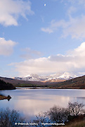 Looking across Llynnau Mymbyr lakes to a snow covered Mount Snowdon on a sunny winter day, Capel Curig, Conwy, Snowdonia, Wales, UK