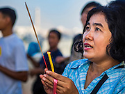 18 NOVEMBER 2015 - BANGKOK, THAILAND: A woman prays at the chedi at the top of Wat Saket during the parade marking the start of the temple's annual fair. Wat Saket is on a man-made hill in the historic section of Bangkok. The temple has golden spire that is 260 feet high which was the highest point in Bangkok for more than 100 years. The temple construction began in the 1800s in the reign of King Rama III and was completed in the reign of King Rama IV. The annual temple fair is held on the 12th lunar month, for nine days around the November full moon. During the fair a red cloth (reminiscent of a monk's robe) is placed around the Golden Mount while the temple grounds hosts Thai traditional theatre, food stalls and traditional shows.      PHOTO BY JACK KURTZ