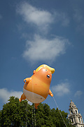 The inflatable balloon called Baby Trump flies above Parliament Square in Westminster, the seat of the UK Parliament, during the US President's visit to the UK, on 13th July 2018, in London, England. Baby Trump is a 20ft high orange blimp depicting the US President as an enraged, smartphone-clutching infant - and given special permission to appear above the capital by London Mayor Sadiq Khan because of its protest rather than artistic nature. It is the brainchild of Graphic designer Matt Bonner.