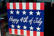 Sign commemorating 4th of July posted in store window. Washington DC USA