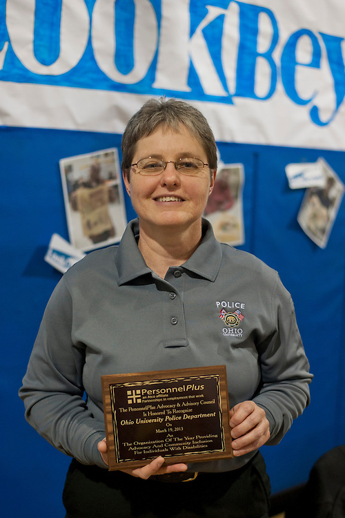 Ohio University Police Department Communications Officer Cathy Hart holds an award given to OUPD during the Athens County Disability Awareness Festival, Tuesday, March 19, 2013. The award was given for OUPD's outstanding advocacy and community inclusion for individuals with disabilities.