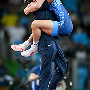 Helen Maroulis, in blue, lept into the arms on her coach after she earned the United States its first Olympic gold in women's wrestling in dramatic fashion, defeating three-time Olympic champion Saori Yoshida of Japan Thursday evening at Carioca Arena 2 during the 2016 Summer Olympics Games in Rio de Janeiro, Brazil.