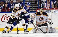 Boston Bruins defenseman Adam McQuaid, left, deflects the puck away from Tampa Bay Lightning's Adam Hall in front of goalie Tuukka Rask, of Finland, during the first period of an NHL hockey game Thursday, Feb. 21, 2013, in Tampa, Fla. (AP Photo/Mike Carlson)