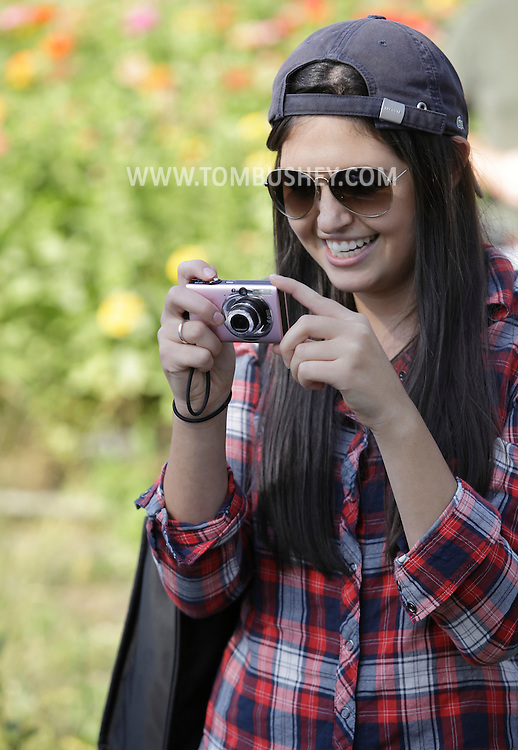New Hampton, New York - A young woman smiles while taking pictures of a pie-eating contest during the celebration of 100 years in business at Soons Orchards and Farm Market  on Oct. 11, 2010. ©Tom Bushey / The Image Works