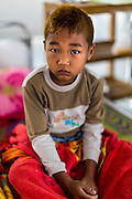 05 MARCH 2014 - MAE SOT, TAK, THAILAND: A boy waits for a medic in the Mae Tao Clinic. The Mae Tao Clinic provides  healthcare to over 150,000 displaced Burmese per year and is the leading healthcare provider for Burmese along the Thai-Myanmar border. Reforms in Myanmar have alllowed NGOs to operate in Myanmar, as a result many NGOs are shifting resources to operations to Myanmar, leaving Burmese migrants and refugees in Thailand vulnerable.     PHOTO BY JACK KURTZ